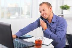 Молодой бизнесмен работая в офисе, сидящ на таблице, говоря на телефоне Стоковые Изображения RF