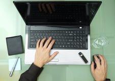 Молодой бизнесмен работая в офисе, сидя на столе с lapto стоковое фото