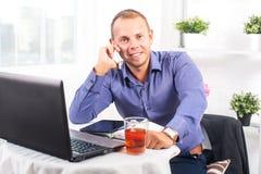 Молодой бизнесмен работая в офисе, сидя на таблице, смотря прямой и говоря на телефоне Стоковое фото RF