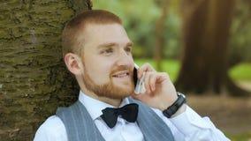Молодой бизнесмен сидит под деревом сток-видео