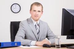 Молодой бизнесмен сидя в ярком офисе Стоковые Изображения RF
