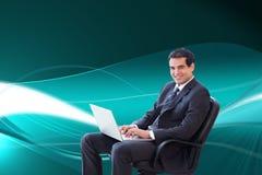 Молодой бизнесмен сидя на кресле работая с компьтер-книжкой Стоковые Изображения