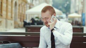 Молодой бизнесмен сидя на стенде работая на согласовании и говоря на мобильном телефоне акции видеоматериалы