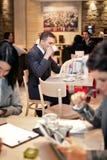 Молодой бизнесмен сидя на таблице в кафе Стоковые Изображения