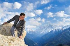 Молодой бизнесмен смотря вниз от верхней части горы Стоковая Фотография RF
