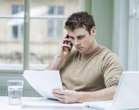 Молодой бизнесмен смотря документы пока использующ мобильный телефон в офисе Стоковое Изображение