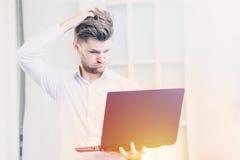 Молодой бизнесмен смотря тетрадь с сотрясенной отрицательной позицией стресса, теплый фильтр компьтер-книжки тона Стоковое фото RF