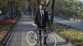 Молодой бизнесмен стоя на переулке города с велосипедом видеоматериал