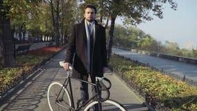 Молодой бизнесмен стоя на переулке города с велосипедом акции видеоматериалы