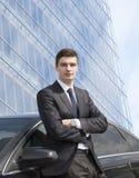 Молодой бизнесмен стоя около его автомобиля Стоковые Изображения