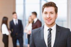 Молодой бизнесмен стоя перед его co Стоковые Фотографии RF