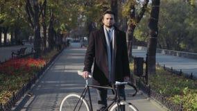 Молодой бизнесмен стоя с велосипедом и взглядом в камере видеоматериал