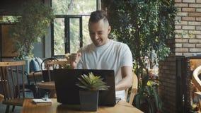 Молодой бизнесмен счастлив из-за начинать успешный проект Укомплектуйте личным составом дело старта новое онлайн в кафе, работая  акции видеоматериалы