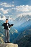 Молодой бизнесмен с его компьтер-книжкой говоря телефоном на mounta Стоковые Фото