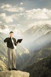 Молодой бизнесмен с его компьтер-книжкой говоря телефоном Стоковые Фотографии RF