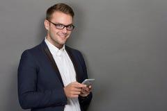 Молодой бизнесмен с мобильным телефоном на его руке стоковая фотография rf