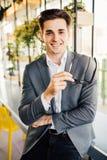 Молодой бизнесмен с стеклами в его оружиях сидя на краю его деревянного стола смотря серьезно на камере Стоковая Фотография RF