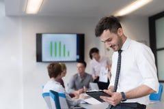 Молодой бизнесмен с таблеткой на конференц-зале офиса Стоковые Изображения RF