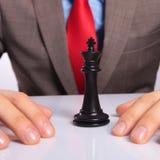 Молодой бизнесмен с черным королем шахмат Стоковые Фотографии RF