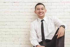 Молодой бизнесмен усмехаясь пока сидящ вскользь стоковые фото
