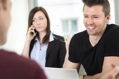 Молодой бизнесмен усмехаясь пока смотрящ коллеги Стоковое Фото