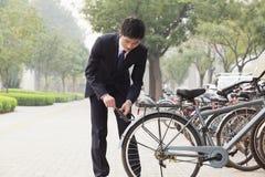 Молодой бизнесмен фиксируя вверх по его велосипеду на улице города в Пекине Стоковая Фотография RF