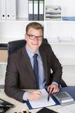 Молодой бизнесмен штемпелюет документ Стоковая Фотография