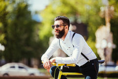 Молодой бородатый битник человека в солнечных очках полагаясь на его велосипеде и смотря отсутствующий пока стоящ на улице города Стоковая Фотография RF