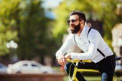 Молодой бородатый битник человека в солнечных очках полагаясь на его велосипеде и смотря отсутствующий пока стоящ на улице города Стоковые Изображения
