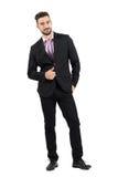 Молодой бородатый успешный человек в костюме с большими пальцами руки вверх усмехаясь на камере Стоковое Изображение RF