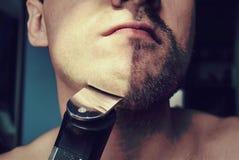 Молодой бородатый человек во время холить Стоковые Изображения