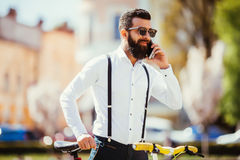 Молодой бородатый человек говоря на мобильном телефоне и усмехаясь пока сидящ около его велосипеда в улице Стоковые Фотографии RF