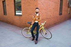 Молодой бородатый человек держа руку на подбородке и смотря камеру пока сидящ около его велосипеда outdoors около кирпичной стены Стоковое Изображение RF