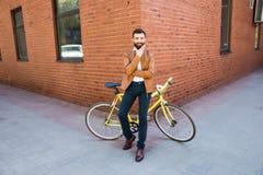 Молодой бородатый человек держа руку на подбородке и смотря камеру пока сидящ около его велосипеда outdoors около кирпичной стены Стоковое Фото