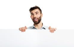 Молодой бородатый человек показывая пустой шильдик, изолированный над белизной Стоковое фото RF