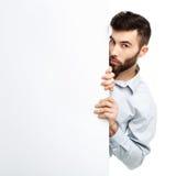 Молодой бородатый человек показывая пустой шильдик, изолированный над белизной Стоковая Фотография RF