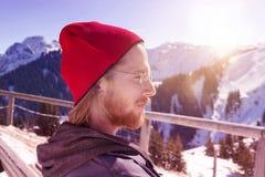 Молодой бородатый человек сидя в солнце окруженном горами Стоковые Фотографии RF