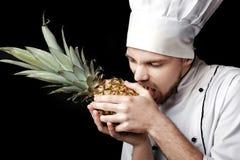 Молодой бородатый шеф-повар человека в белой форме держит свежий ананас на черной предпосылке Стоковые Изображения RF