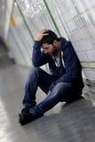 Молодой больной человек потерял страдая депрессию сидя на земном тоннеле метро улицы Стоковая Фотография RF