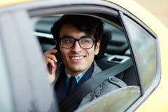 Молодой ближневосточный бизнесмен вызывая телефоном в автомобиле Стоковое Изображение RF
