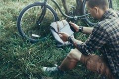 Молодой велосипедист Гая сидит на луге лета около велосипеда, держа и смотря концепцию назначения перемещения воссоздания таблетк Стоковые Фото