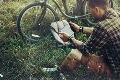 Молодой велосипедист Гая сидит на луге лета около велосипеда, держа и смотря концепцию назначения перемещения воссоздания таблетк Стоковая Фотография