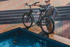 Молодой велосипедист положил его велосипед на край концепции ежедневного образа жизни фонтана города городской отдыхая стоковые изображения