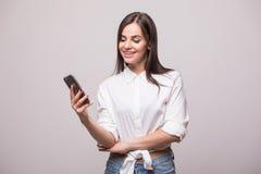 Молодой взгляд девушки красоты на телефоне Стоковое Изображение