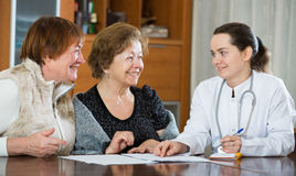 Молодой врач получая зрелых пациентов в клинике Стоковые Изображения RF