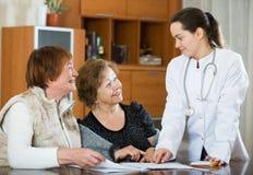 Молодой врач получая зрелых пациентов в клинике Стоковое Изображение