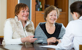 Молодой врач получая зрелых пациентов в клинике Стоковая Фотография