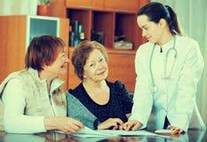 Молодой врач получая зрелых пациентов в клинике стоковые фото