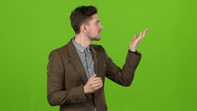 Молодой вручитель в студии говорит прогноз погоды правильно зеленый экран видеоматериал