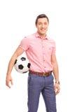 Молодой вскользь парень держа футбол Стоковая Фотография RF